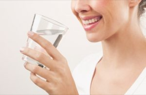Close up of smiling woman drinking water