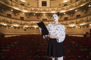 retrato-de-femininas-mime-ficar-em-um-auditorio-segurando-roteiro_23-2147891529