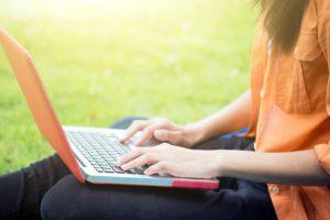 jovem-mulher-usando-computador-em-oculos-verdes-no-parque_1421-165